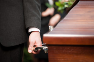 carrying casket at funeral to cemetery after filing a lawsuit for wrongful death with attorney